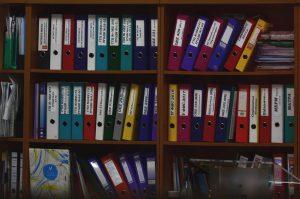 Different coloured document folders on a bookshelf