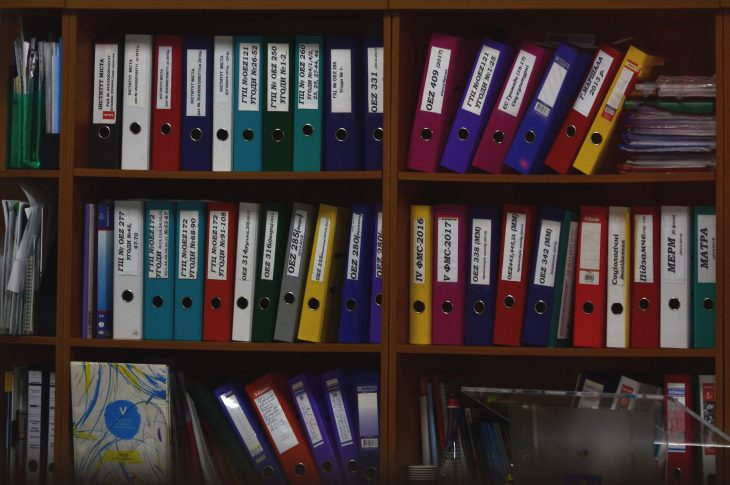 Different coloured document folders on a bookshelf