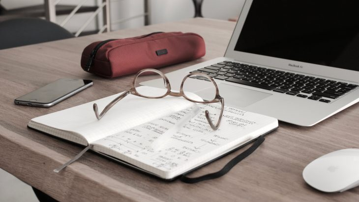 Laptop, notebook, and glasses on a desk